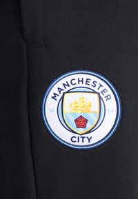 Puma - MANCHESTER CITY ICONIC GRAPHIC TRACK PANTS - Tracksuit bottoms - black/spectra yellow - 2