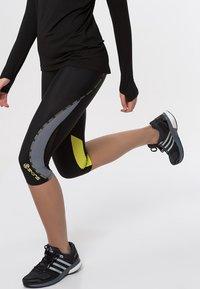 Skins - DNAMIC - 3/4 sports trousers - black/limoncello - 3