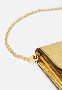 Lauren Ralph Lauren - ADAIR CROSSBODY SMALL - Wallet - antique gold-coloured - 4