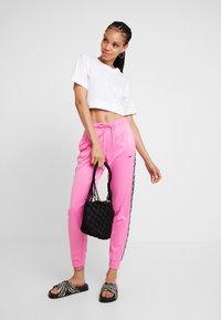 Nike Sportswear - JOGGER LOGO TAPE - Pantalon de survêtement - china rose/black - 2