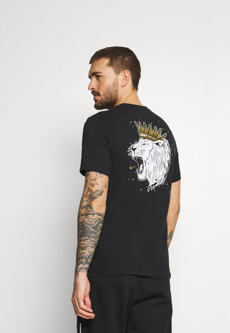 Nike Performance - DRY LOGO TEE - Print T-shirt - black/gold dart