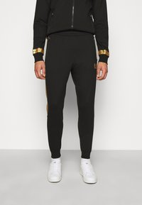 EA7 Emporio Armani - Tracksuit bottoms - black/gold - 0