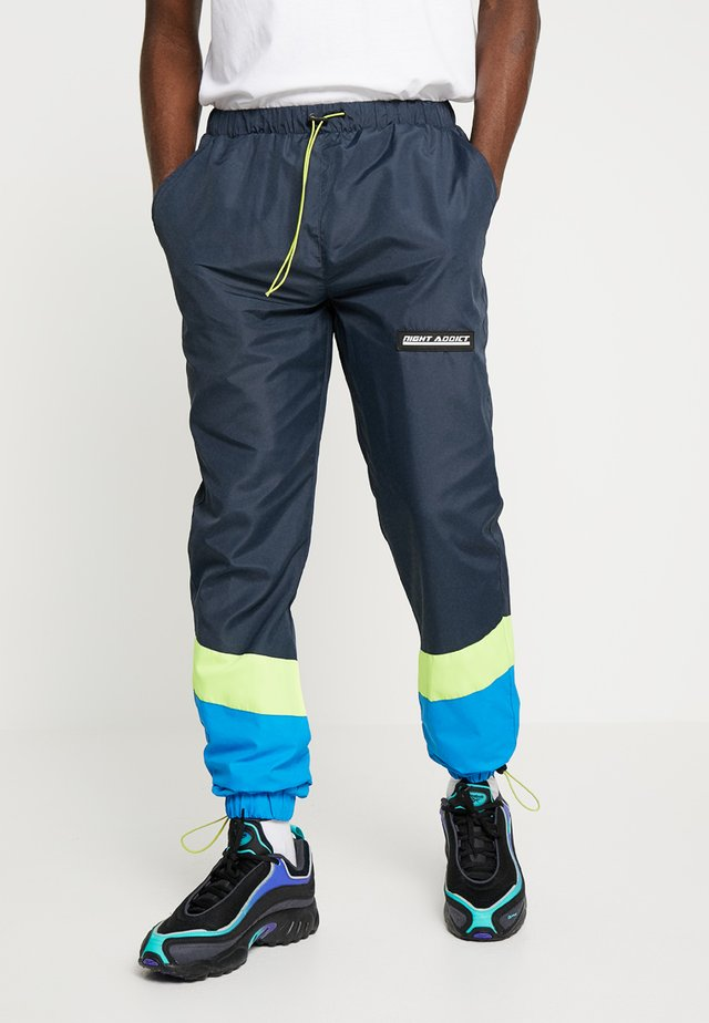 NARUSS - Pantalon de survêtement - navy/neon yellow