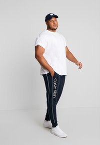 Calvin Klein - LOGO PRINT PANT - Träningsbyxor - blue - 1