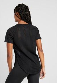 Nike Performance - TOP GLAM - T-shirt z nadrukiem - black/metallic gold - 2
