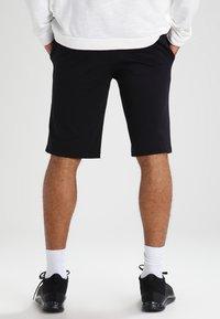 Nike Sportswear - CLUB - Tracksuit bottoms - schwarz/weiß - 2