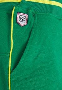 Schott - Tracksuit bottoms - green/yellow - 2