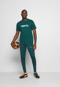 Nike Performance - PANT SOCK CUFF - Pantalon de survêtement - dark atomic teal/black/electro orange - 1