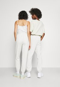 Jack & Jones - JJITOBIAS PANTS UNISEX - Tracksuit bottoms - white melange - 2