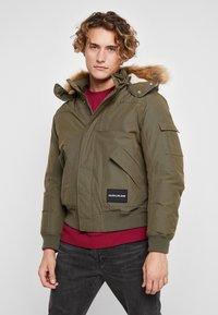 Calvin Klein Jeans - FUR TRIMMED HOODED DOWN BOMBER - Down jacket - dark green - 0