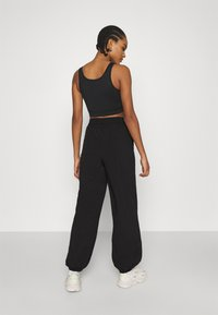 NA-KD - NA-KD X ZALANDO EXCLUSIVE - SPORTY FABRIC PANTS - Tracksuit bottoms - black - 2