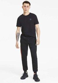 Puma - Pantalon de survêtement - cotton black - 1