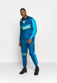 Puma - TRAIN PANT - Tracksuit bottoms - digi blue/energy blue/fizzy yellow