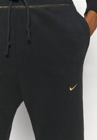 Nike Performance - Pantalones deportivos - black/metallic gold - 5