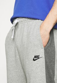 Nike Sportswear - Träningsbyxor - dark grey heather/charcoal heather/white/black - 5