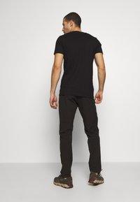 Salomon - WAYFARER AS TAPERED PANT - Pantalon classique - black - 2