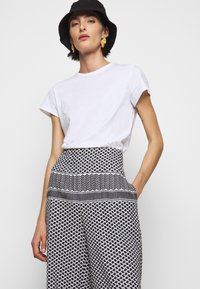 CECILIE copenhagen - BASIC TROUSERS - Trousers - black/white - 3