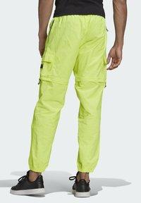 adidas Originals - R.Y.V. UTILITY 2-IN-1 TRACKSUIT BOTTOMS - Träningsbyxor - yellow - 1