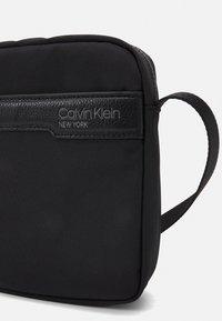 Calvin Klein - REPORTER UNISEX - Taška spříčným popruhem - black - 3