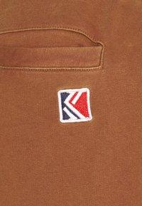 Karl Kani - SMALL SIGNATURE UNISEX - Tracksuit bottoms - dark orange - 2