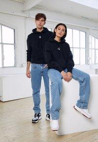 Calvin Klein Jeans - GRAPHIC HOODIE UNISEX - Sweatshirt - black - 5