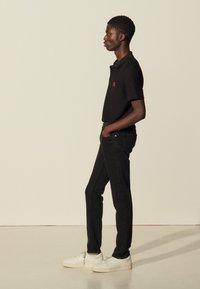 sandro - SLIM - Slim fit jeans - black denim - 1