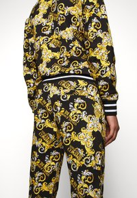 Versace Jeans Couture - FLEECE NEW LOGO - Tracksuit bottoms - nero - 4