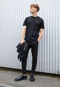 HUGO - DOAK - Teplákové kalhoty - black / gold - 3