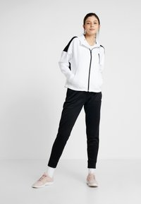 The North Face - SURGENT CUFFEDPANT - Tracksuit bottoms - black - 1