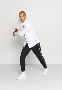 Lacoste Sport - PANT TAPERED - Tracksuit bottoms - black - 1