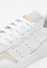 adidas Originals - SUPER COURT SPORTS INSPIRED SHOES UNISEX - Zapatillas - footwear white/gold metallic - 5