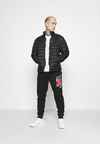 Calvin Klein - TEXT REVERSED  - Tracksuit bottoms - black - 1
