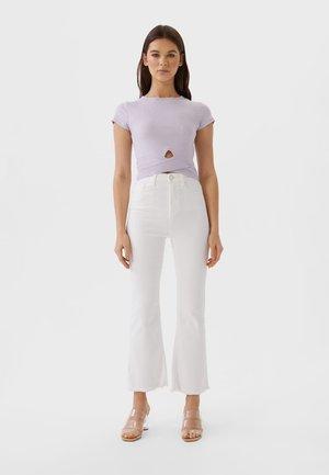 MIT SCHLAG - Flared Jeans - white