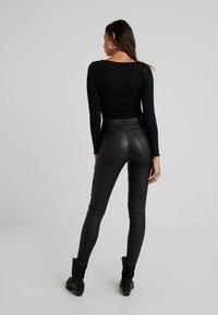 Vero Moda - VMSOPHIA COATED PANTS - Trousers - black - 2
