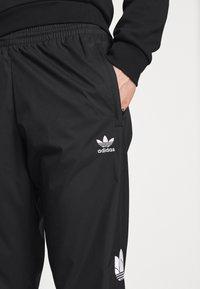 adidas Originals - ADICOLOR 3D TREFOIL 3-STRIPES TRACK PANTS - Tracksuit bottoms - black - 4