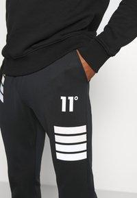 11 DEGREES - NANO REFLECTIVE STRIPE TRACK PANTS - Tracksuit bottoms - black - 4
