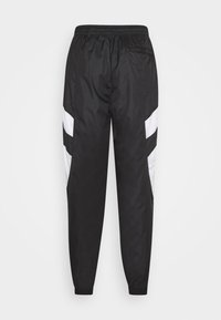 Puma - WORLDHOOD TRACK PANTS - Tracksuit bottoms - black - 1