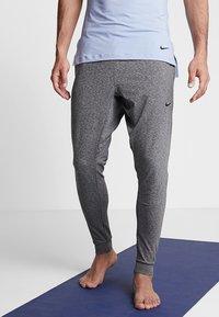 Nike Performance - M NK DRY PANT HPR DRY LT YOGA - Tracksuit bottoms - black - 0