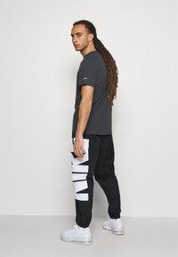Nike Performance - STARTING PANT - Tracksuit bottoms - black/white - 2