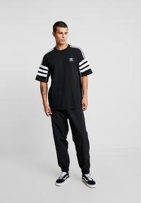 adidas Originals - REVEAL YOUR VOICE - Tracksuit bottoms - black - 1