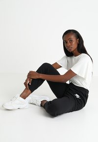 Nike Sportswear - RALLY - Tracksuit bottoms - black - 1