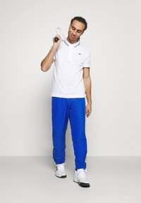 Lacoste Sport - TENNIS PANT TAPERED - Tracksuit bottoms - lazuli/black/white - 1