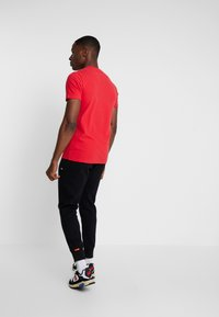 Superdry - COLLECTIVE - Tracksuit bottoms - black - 2