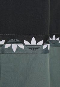 adidas Originals - SLICE TREFOIL ADICOLOR PRIMEGREEN ORIGINALS SLIM TRACK - Tracksuit bottoms - black/blue oxide - 6