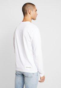 Calvin Klein Jeans - ON THE BACK LONGSLEEVE - Top sdlouhým rukávem - bright white/black - 2