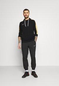 Nike Performance - DRY HOODIE - Langærmede T-shirts - black/saturn gold/white - 1