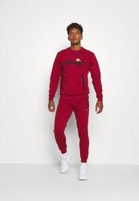 Ellesse - OSTERIA - Pantalon de survêtement - dark red - 1