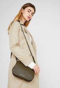 Calvin Klein - MELLOW SADDLE BAG - Across body bag - green - 1