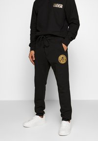 Versace Jeans Couture - PATCH JOGGERS - Verryttelyhousut - black - 0