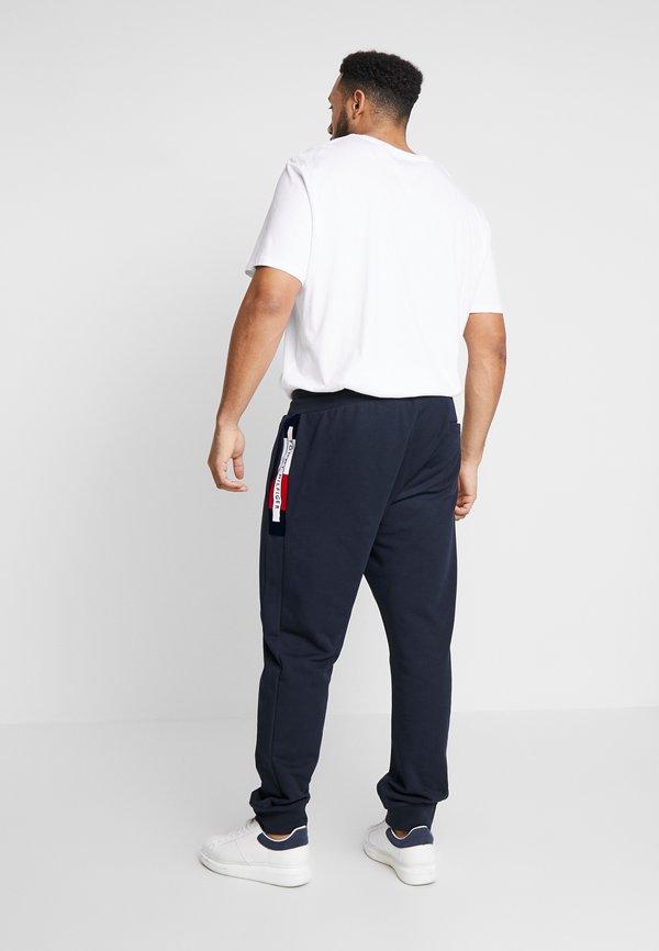 Tommy Hilfiger FLOCKED - Spodnie treningowe - blue/granatowy Odzież Męska SZZS